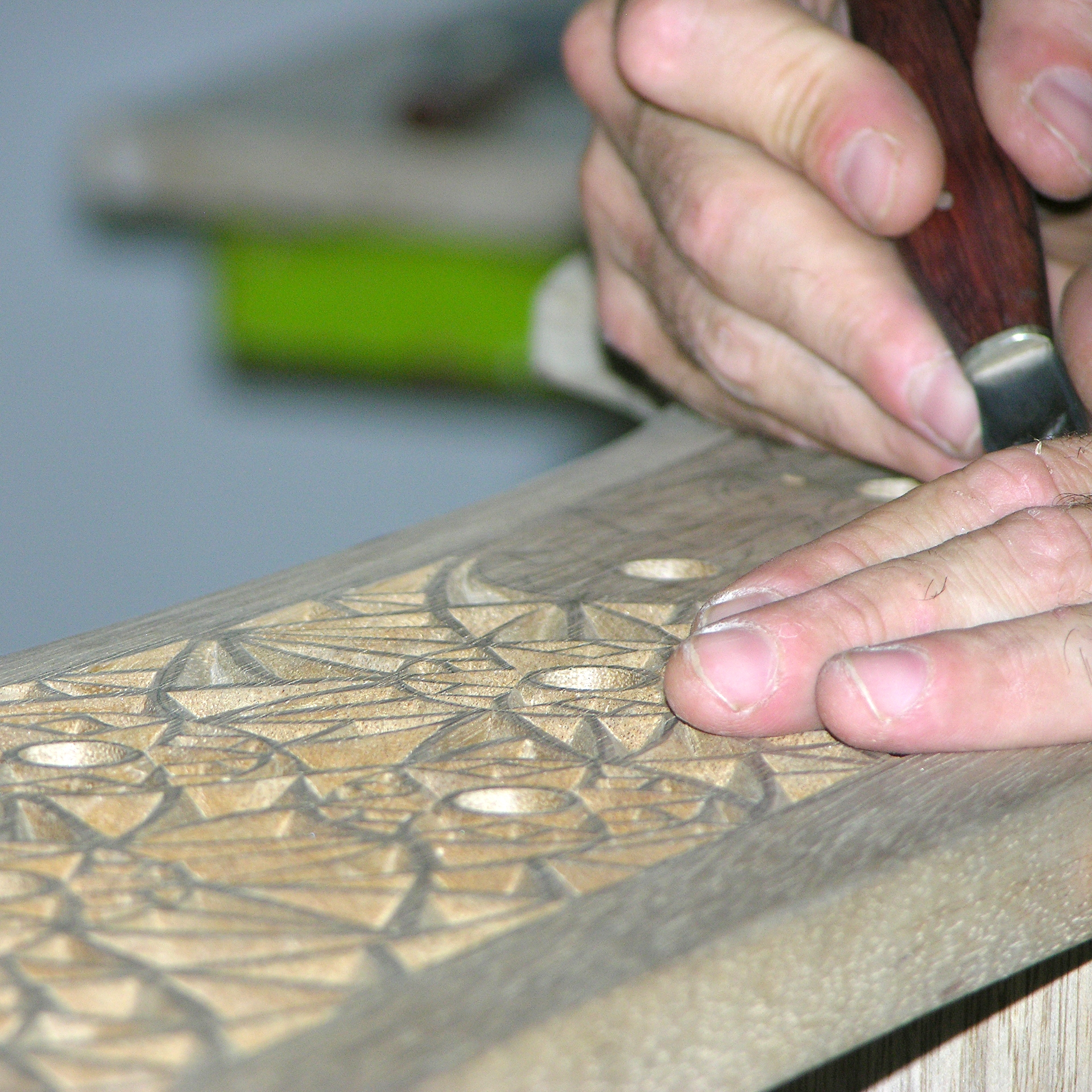 Courses: Hands carve an intricate design into wood