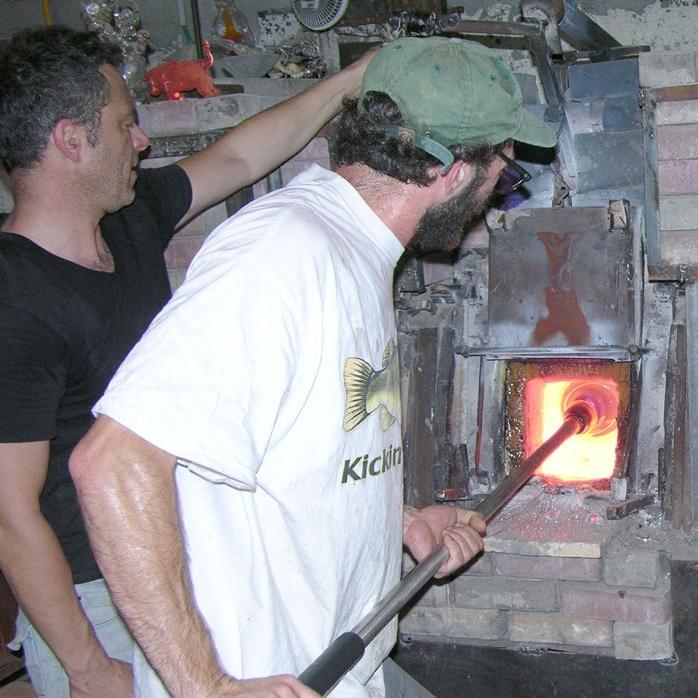 Glassblowers fire glass in the kiln